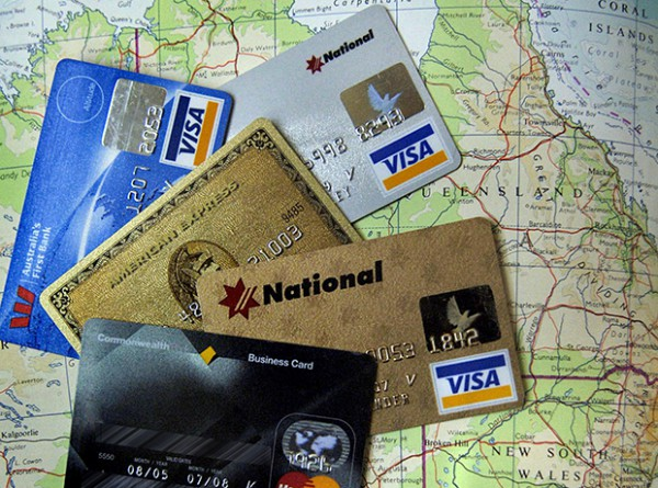 Various Australian credit cards are arranged on an atlas map