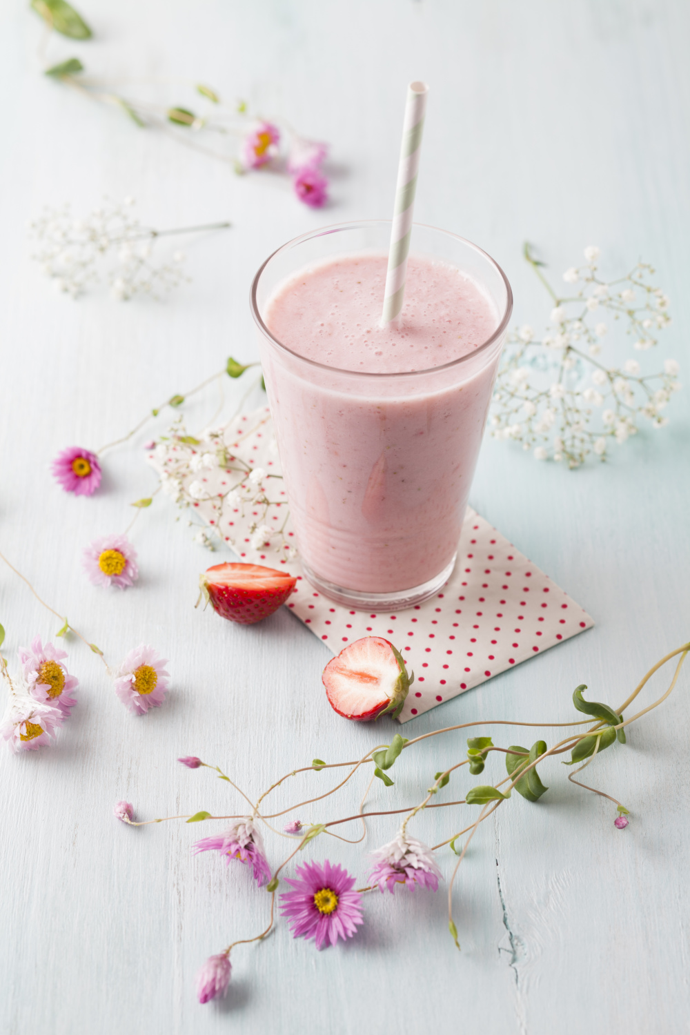 Glass of strawberry smoothie with cornflower blossom