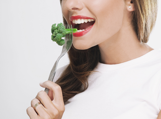Close-up of a woman eating broccoli