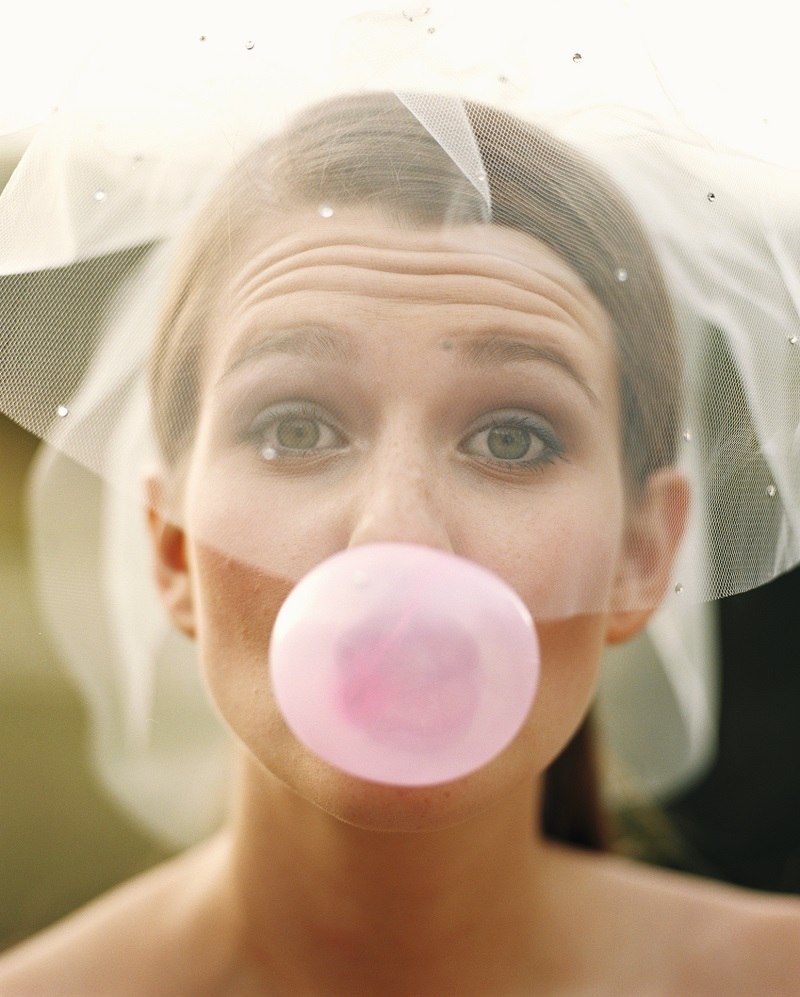 Young woman wearing bridal veil, blowing bubble, close up, portrait