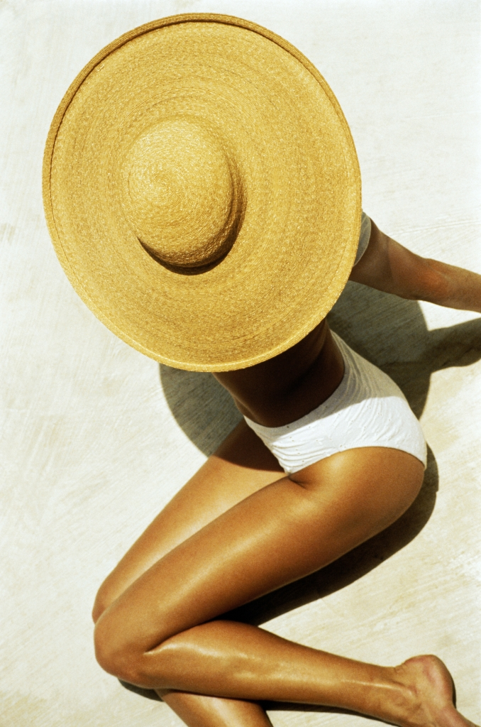 Overhead view of woman in white bikini and large straw hat