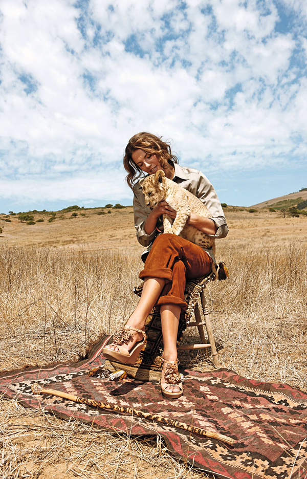 Woman holding lion cub and sitting on stool in steppe